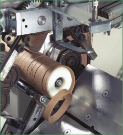 Machine cutting a paper core into designated equal lengths